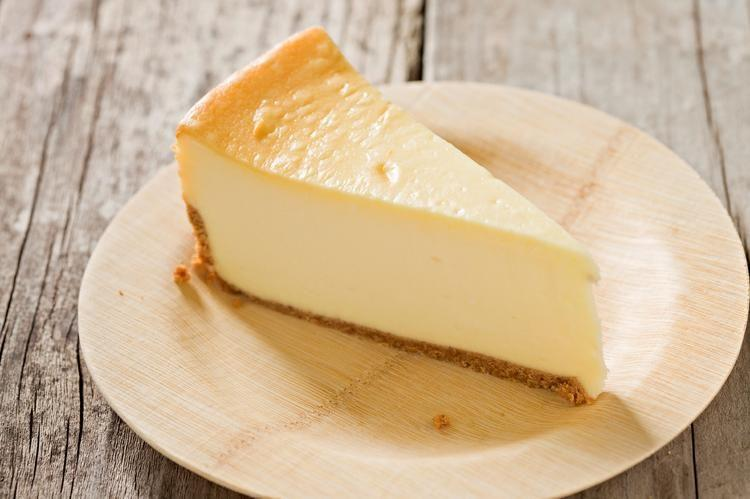 new york cheese cake on white plate sitting on wooden table
